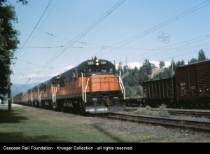 MILW GE U25B locomotives 388, 385, 381, and 383 lead a train through Cle Elum in August 1965.  Note the dynamometer car behind the engines.  Duplicate slide by an unidentified photographer in the Cascade Rail Foundation Paul Krueger Collection.